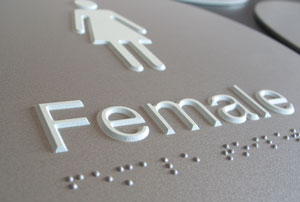 Female toilet sign with braille